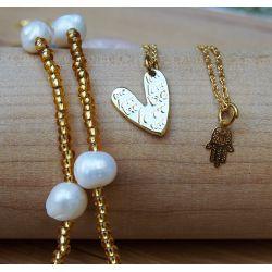 Détail élégant collier triple chaîne doré perles et pendentifs